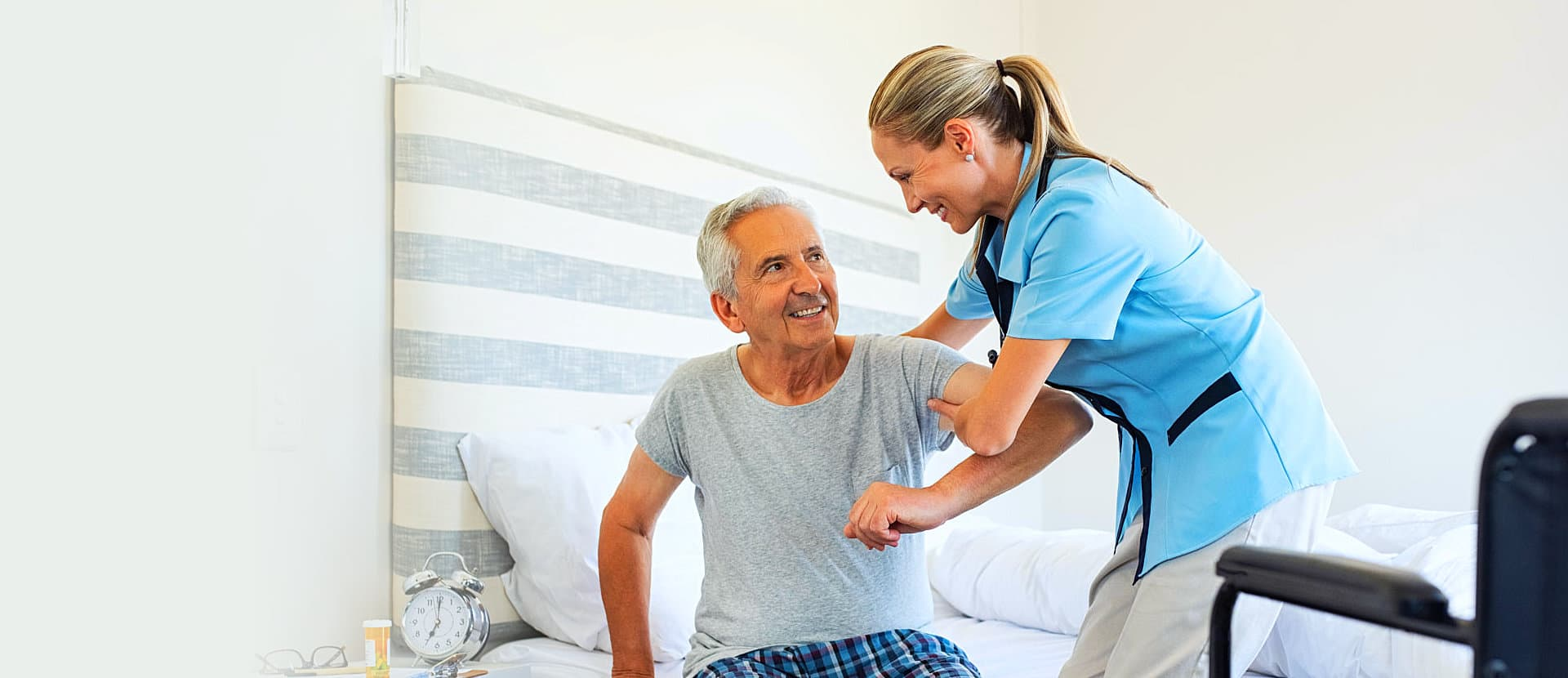 caregiver helping senior man to stand