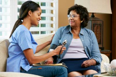 nurse giving blood pressure test on a senior woman