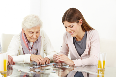 young lady playing puzzle with a senior woman