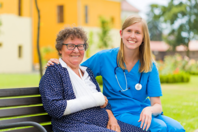 nurse and a senior woman sitting on a bench