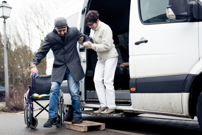nurse helping a senior get off a van and into his wheelchair