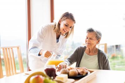 caregiver pouring orange juice to a senior woman's glass
