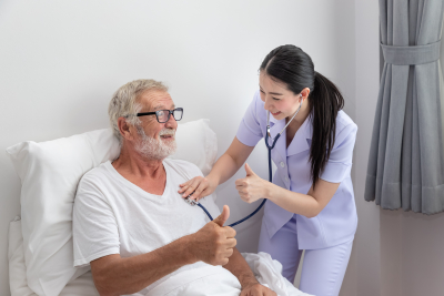 nurse examining an elder man on a bed and giving thumbs up
