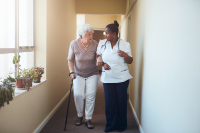 caregiver walking with her senior patient